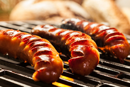 Grilling sausages on barbecue grill. Selective focus Фото со стока