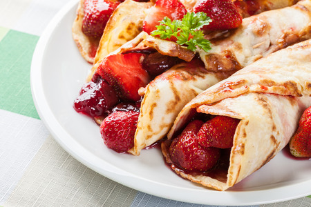 filled: Traditional crepes served with strawberries on a plate Stock Photo