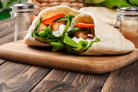 Pita bread with falafel and fresh vegetables on wooden table Stockfoto