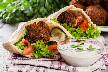 Pita bread with falafel and fresh vegetables on wooden table Фото со стока