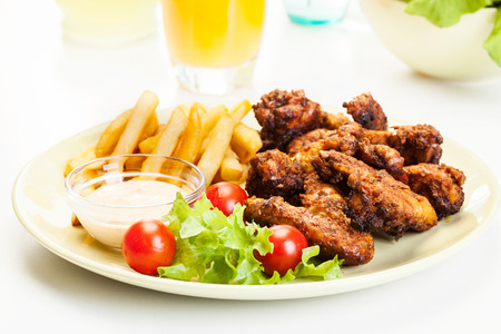 Chicken wings with fries french and spicy sauce on a plate Stockfoto
