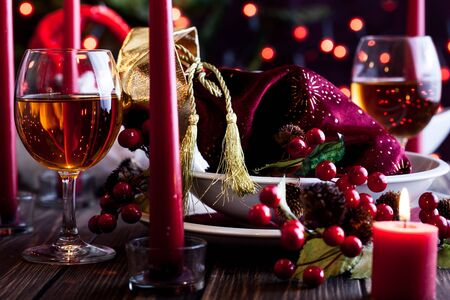 candle light table setting: Christmas gift in dishware at the wooden table