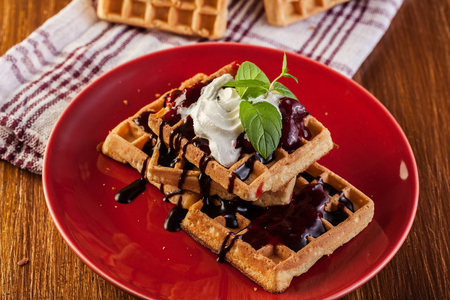 Waffles with chocolate sauce, whipped cream and confiture on plate