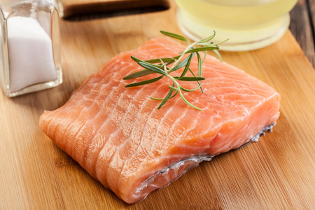 filet: Fresh raw salmon filet on wooden cutting board Stock Photo
