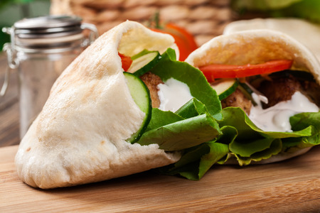 Pita bread with falafel and fresh vegetables on wooden table Stock Photo