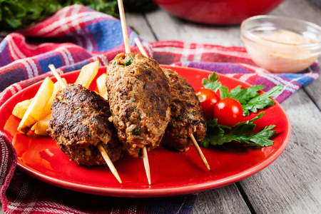 barbecued: Barbecued kofta with fries on a plate. Selective focus Stock Photo