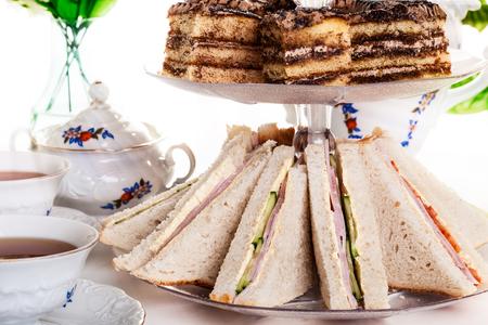 tea party: High tea set with dessert. Focus on sandwich
