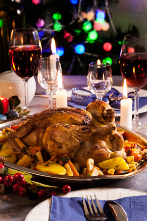 Baked whole chicken for Christmas dinner on festive table Stock Photo