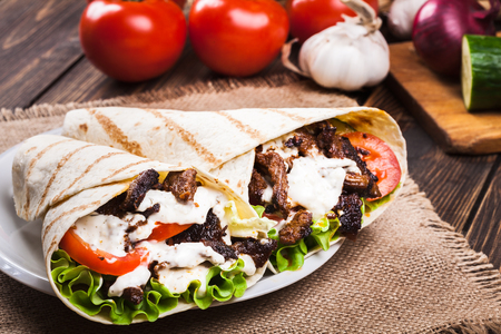 Tasty fresh wrap sandwich with beef, vegetables and tzatziki sauce