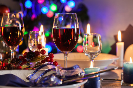 candle light table setting: Glass of wine on the christmas table. Shallow depth of field