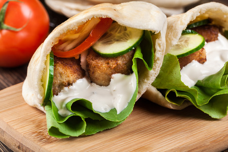 falafel: Pita bread with falafel and fresh vegetables on wooden table Stock Photo