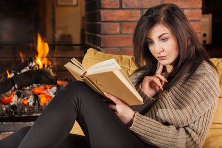 fireplace: Young woman reading a book by fireplace Stock Photo