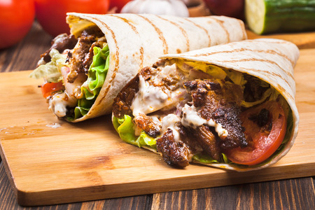 tortilla wrap: Tasty fresh wrap sandwich with beef, vegetables and tzatziki sauce