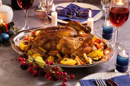 Baked whole chicken for Christmas dinner on festive table Standard-Bild