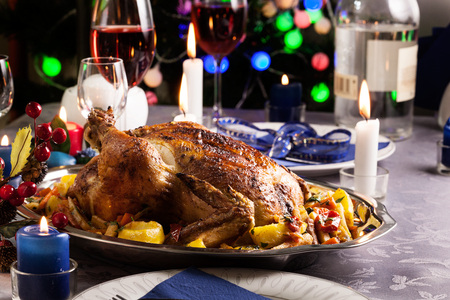 Baked whole chicken for Christmas dinner on festive table Фото со стока