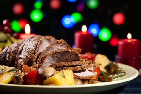 comida de navidad: Asado de cerdo jugosa en la tabla de vacaciones. Poca profundidad de campo
