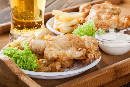 fish and chips: Pescado y patatas fritas con salsa tártara en una bandeja tradicional