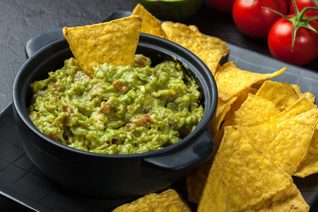Bowl of guacamole with corn chips on a black table Фото со стока