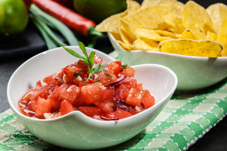 chips and salsa: Bowl of fresh salsa with tortilla chips on a table