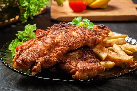 comida inglesa: El pescado frito en pasta crujientes con patatas fritas en un plato