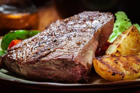 carne asada: Las porciones de filete de carne a la parrilla servido con patatas asadas y pimentón Foto de archivo