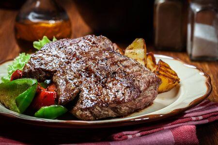 Las porciones de filete de carne a la parrilla servido con patatas asadas y pimentón