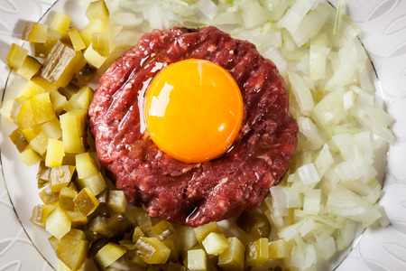 steak tartare: Steak tartare with egg yolk, onions and pickles on a plate Stock Photo