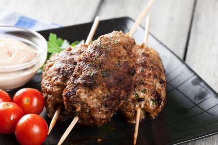 Kofta asado a la parilla con las verduras en un plato. Enfoque selectivo Foto de archivo