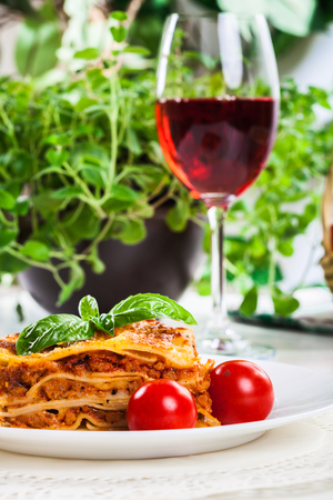 carne picada: Piece of tasty hot lasagna with red wine. Selective focus