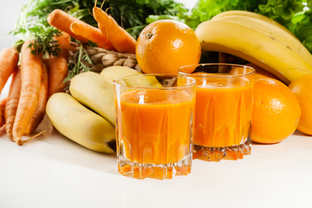 vitamines: Glass of fruit juice with orange, carrots and banana on a table