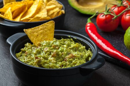 corn chips: Bowl of guacamole with corn chips on a black table Stock Photo