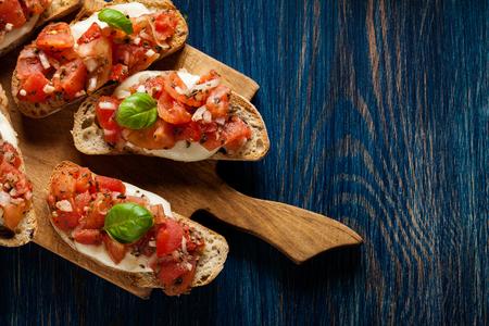 Italiaanse bruschetta met geroosterde tomaten, mozzarella kaas en kruiden op een snijplank Stockfoto