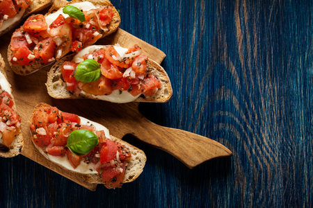 Italian bruschetta with roasted tomatoes, mozzarella cheese and herbs on a cutting board Stockfoto