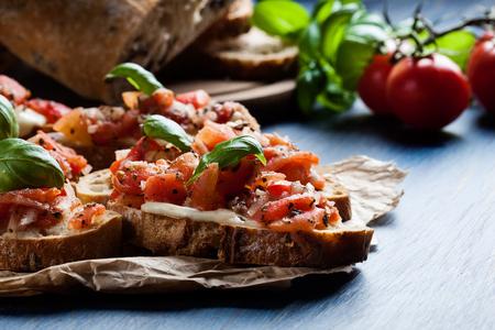 ロースト トマト、モッツアレラ チーズ、ハーブを紙の上のイタリアのブルスケッタ