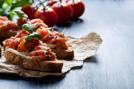 Italian bruschetta with roasted tomatoes, mozzarella cheese and herbs on a paper
