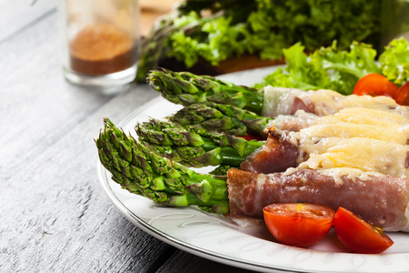 hams: Baked green asparagus with prosciutto and cheese on a plate