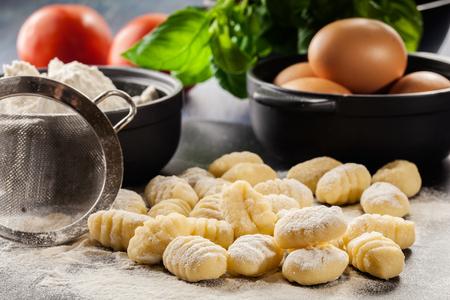 Ongekookte zelfgemaakte gnocchi op zwarte snijplank Stockfoto - 62499621