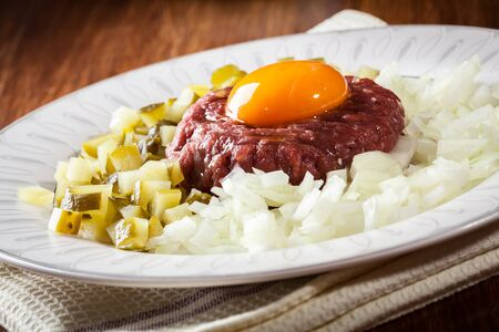 Steak tartare with egg yolk, onions and pickles on a plate Stock Photo