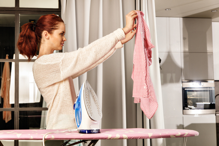 woman ironing: Red-haired young beautiful woman ironing clothes. Housework concept Stock Photo
