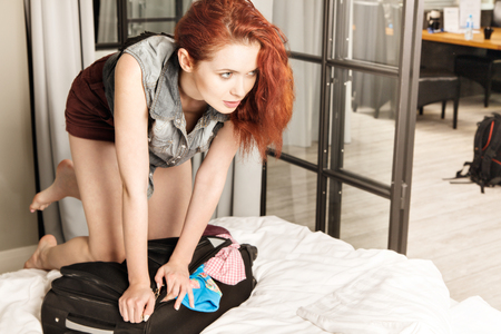 overfilled: Attractive red-haired young woman packing a travel bag before going on holiday. Life style concept.
