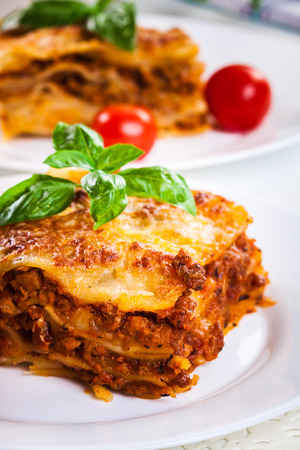 Piece of tasty hot lasagna with red wine. Selective focus