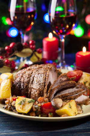 dinner food: Juicy roast pork on the holiday table. Shallow depth of field