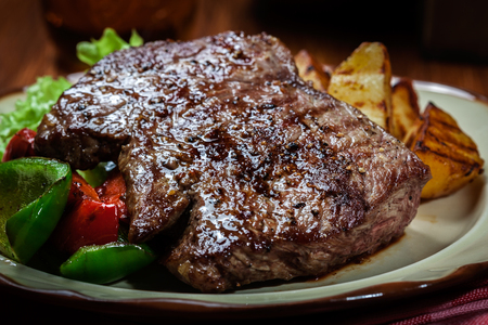 Portions of grilled beef steak served with grilled potatoes and paprika Stock Photo