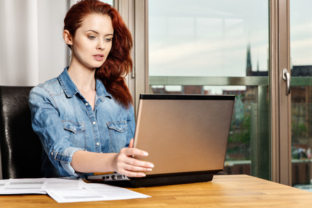 Red-haired young business woman or student girl working with documents and laptop near window. Business concept