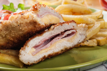 cordon: Cutlet Cordon Bleu with pork loin served with French fries and salad on a plate