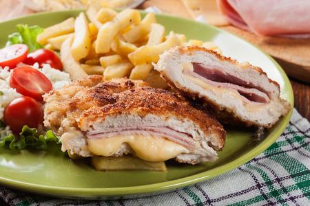 Kotelet Cordon Bleu met varkenslende geserveerd met frites en salade op een plaat