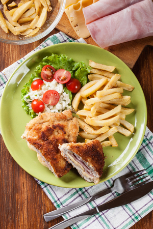 Cutlet Cordon Bleu with pork loin served with French fries and salad on a plate. Top view