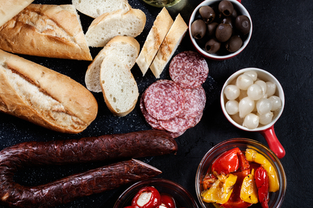 Spanish tapas with slices jamon serrano and grilled pepper. Also olives, salami, pickled onions, and peppers stuffed with cheese. Spanish cuisine. Top view Stock Photo