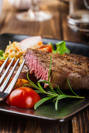 roast potatoes: Succulent portion of beef steak served with roast potatoes Stock Photo