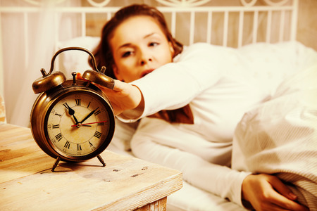 turning off: Young woman in bed turning off alarm clock